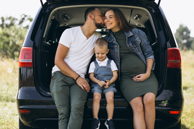Marito con moglie incinta e il loro figlio seduto in macchina