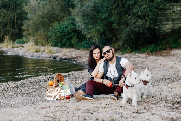Marito con una bella moglie che cammina con i loro cani bianchi nel parco