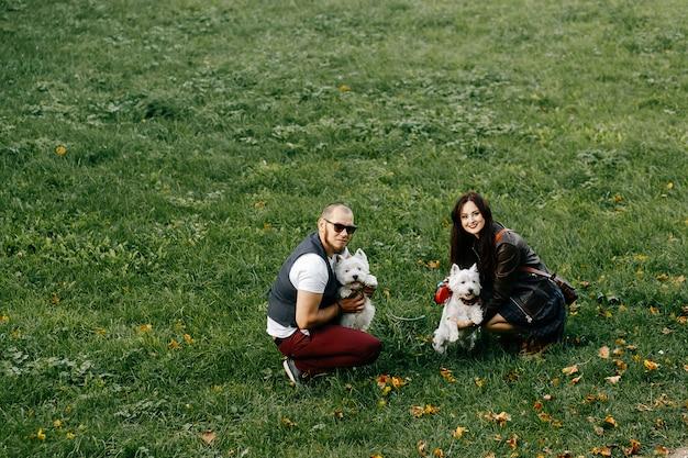 Marito e moglie che camminano i loro animali domestici nel parco di estate su erba verde