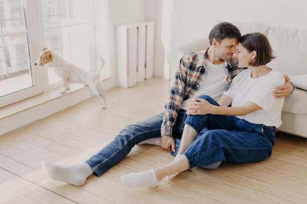 Marito e moglie lieti abbracciano e baciano, hanno buoni rapporti, siedono sul pavimento di legno vicino al divano