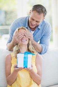 Marito moglie sorprendente con un regalo nel soggiorno