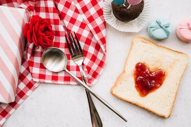 Marmellata a forma di cuore su pane tostato con forchetta e cucchiaio