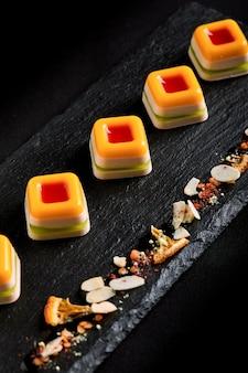 Marmellata colorata, disposta in una bella linea su un piatto nero. spazio alimentare