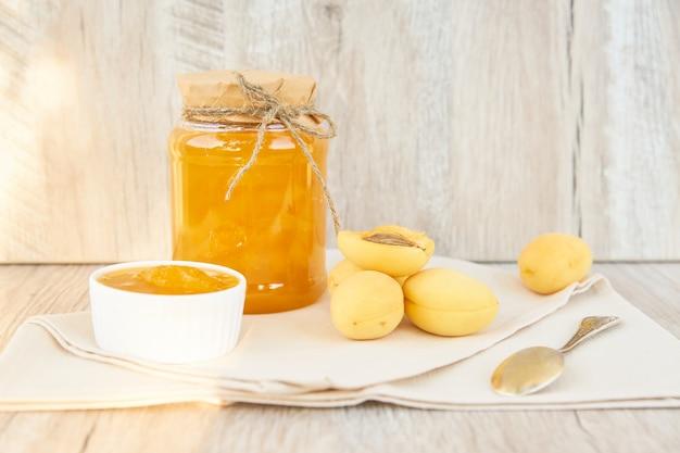 Marmellata di albicocche organica fatta casa in barattolo di vetro e albicocche mature sulla tavola rustica di legno