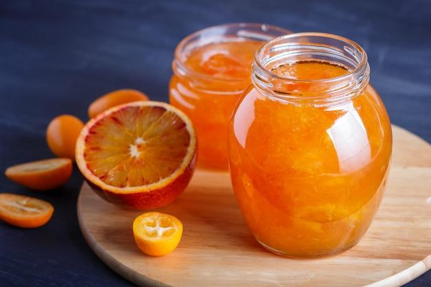 Marmellata di arance e kumquat in un barattolo di vetro con frutta fresca su una tavola di cucina in legno.