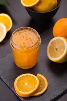 Marmellata di arance fatta in casa in un barattolo su una pietra nera