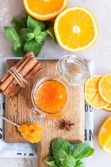 Marmellata di arance in barattolo di vetro, fette di frutta arancione, menta e spezie su grigio chiaro
