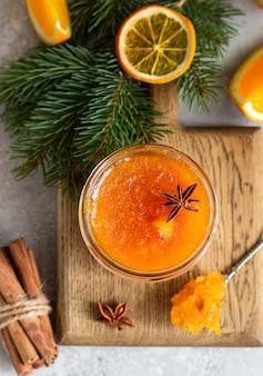 Marmellata di arance in un barattolo di vetro con spezie invernali e rami di abete.