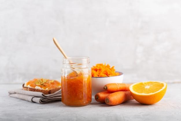 Marmellata di carote con succo d'arancia su uno sfondo grigio