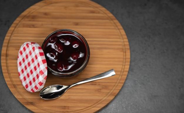 Marmellata di ciliegie, gelatina di ciliegie in un barattolo di vetro con un rosso aperto