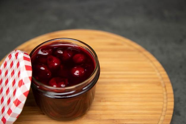 Marmellata di ciliegie in un vaso di vetro con un coperchio aperto di colore rosso su una tavola di legno, una tavola.