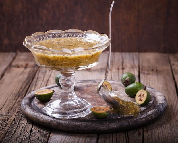 Marmellata di feijoa in un vaso di vetro su una tavola di legno