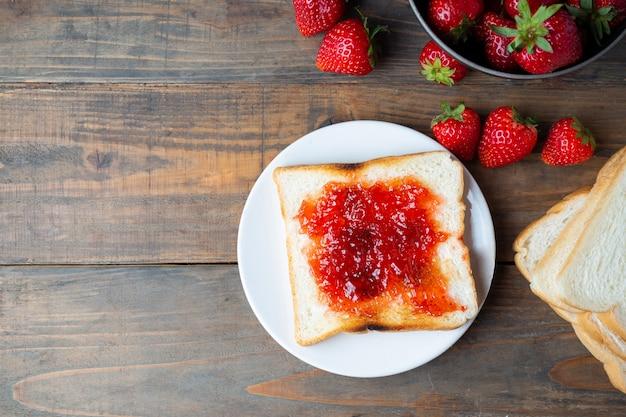 Marmellata di fragole con pane tostato per colazione.