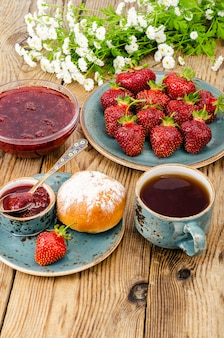 Marmellata di fragole dolce rossa matura, frutti di bosco freschi sulla tavola di legno. foto di studio