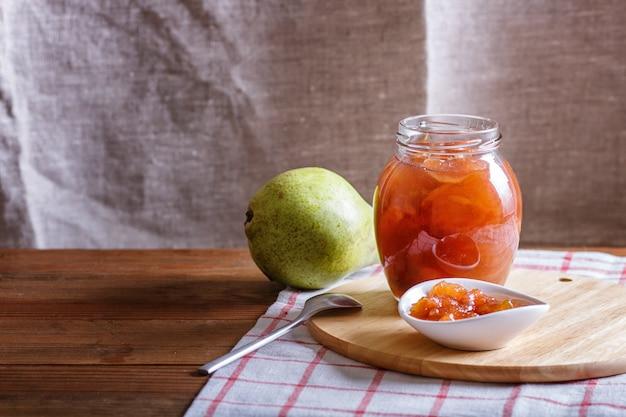 Marmellata di pere in un barattolo di vetro su una tovaglia di lino su un tavolo di legno
