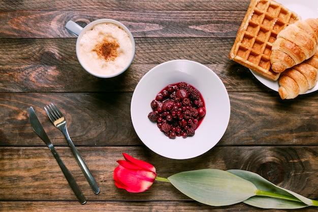 Marmellata in ciotola, fiori freschi, panetteria, posate e tazza di bevanda