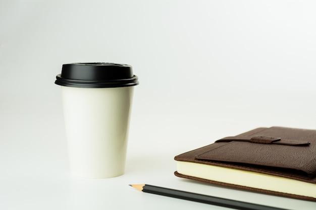 Marrone della tazza di caffè e un taccuino di cuoio sul fondo bianco dello scrittorio con lo spazio della copia