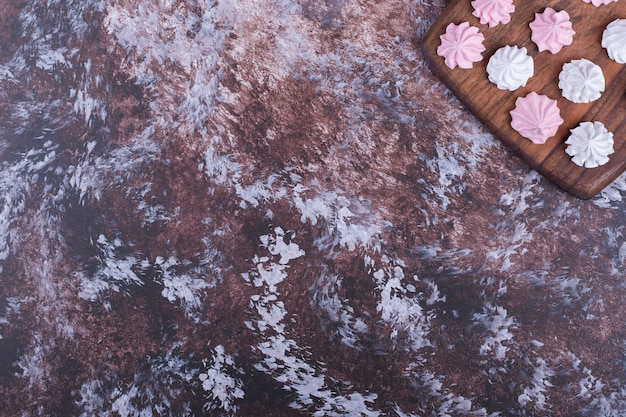Marshmallow a forma di fiore bianco e rosa su un piatto di legno.