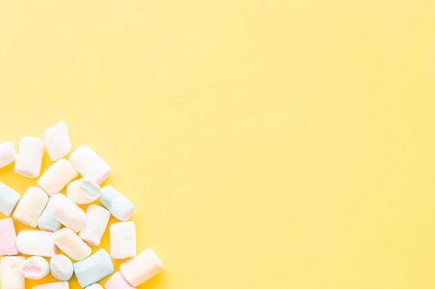 Marshmallow all'angolo dello sfondo giallo