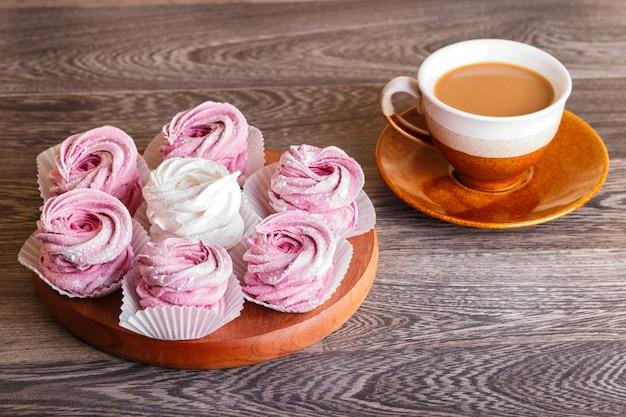 Marshmallow bianco e rosa (zephyr) su una tavola di legno rotonda con una tazza di caffè