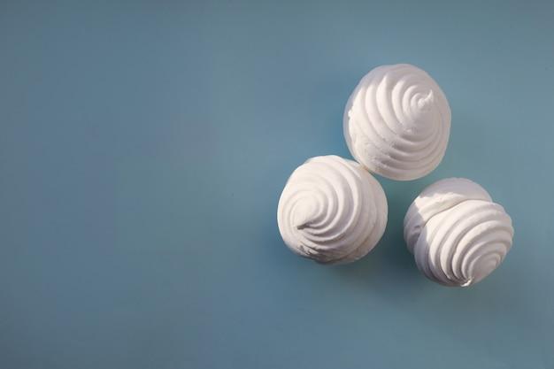 Marshmallow bianco su sfondo blu. flat lay, copia spazio