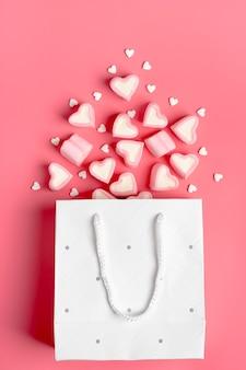 Marshmallow, caramelle a forma di cuore versato dal sacchetto di carta su sfondo rosa buon san valentino