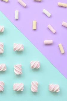 Marshmallow colorato disposto su carta viola e blu