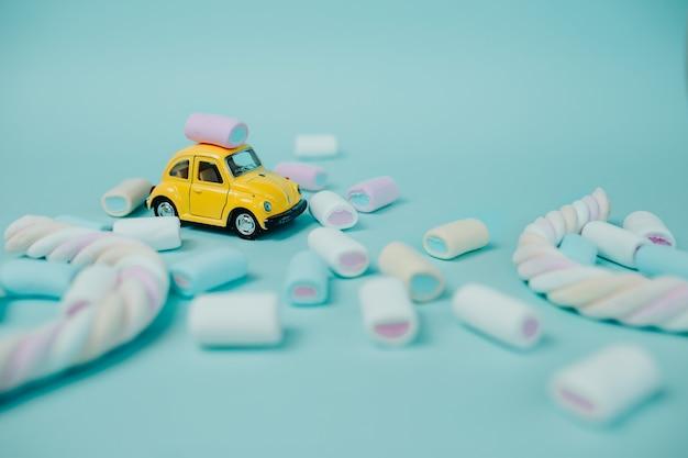 Marshmallow colorato. molte caramelle sul tavolo. macchinina gialla con marshmallow attorcigliata e caramelle intorno.
