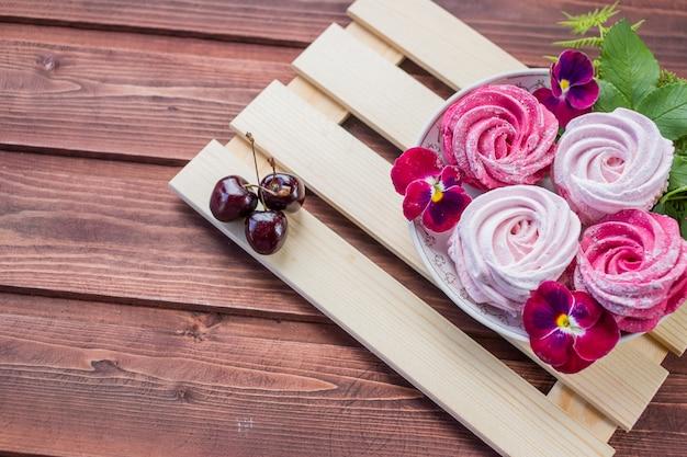 Marshmallow con bacche di ciliegio e fiori su fondo in legno chiaro