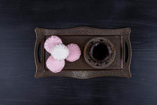 Marshmallow con un bicchiere di tè in un piatto metallico, vista dall'alto