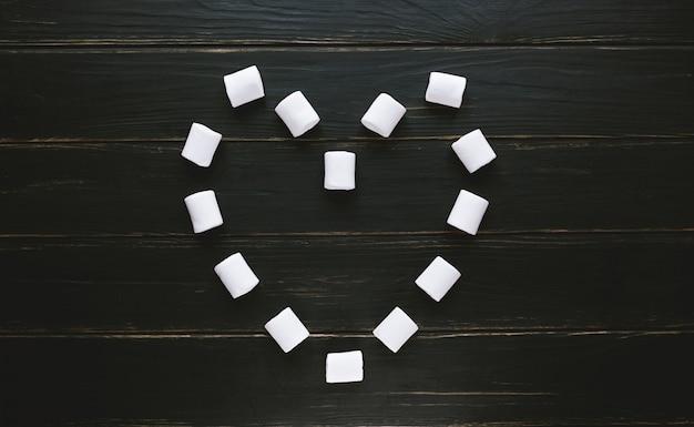 Marshmallow esposto sotto forma di cuore su un tavolo di legno nero