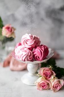 Marshmallow fatti in casa da bacche su un supporto e un mazzo di fiori