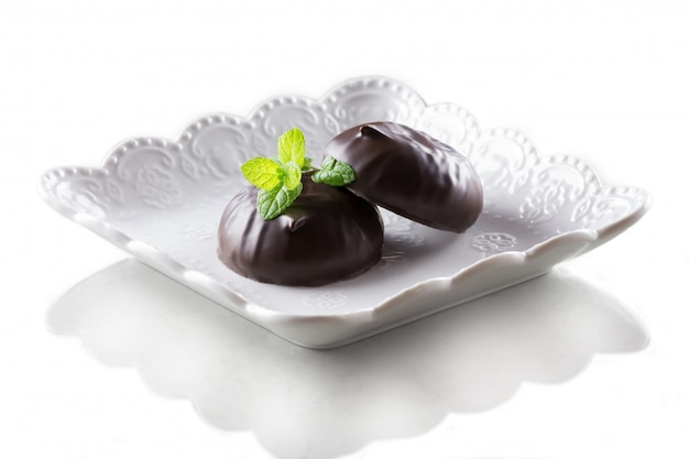 Marshmallow in cioccolato e una foglia di menta isolato su uno sfondo bianco