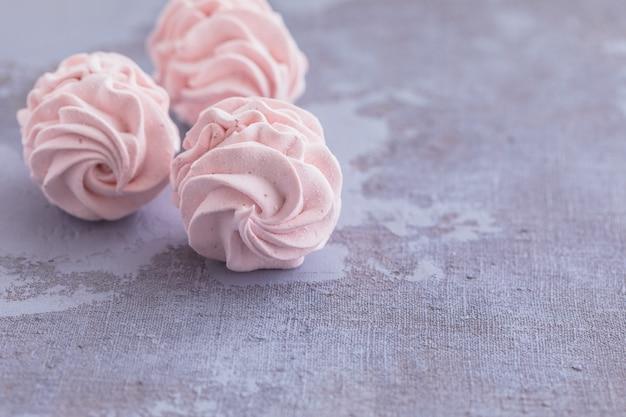 Marshmallow o zephyr casalingo russo tradizionale del merengue su un piatto su fondo concreto