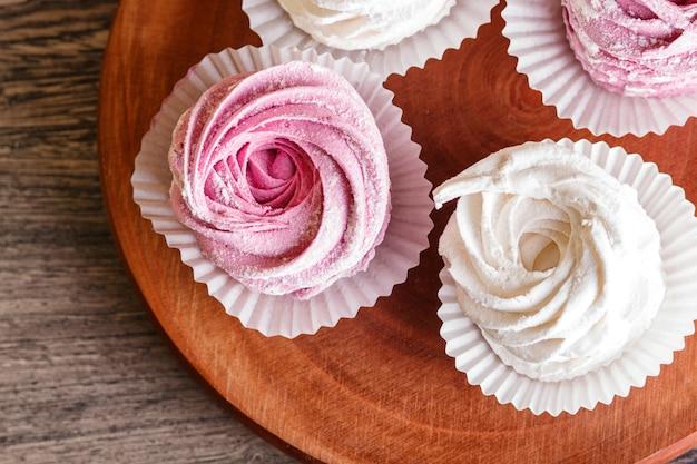 Marshmallow rosa e bianco su una tavola di legno rotonda
