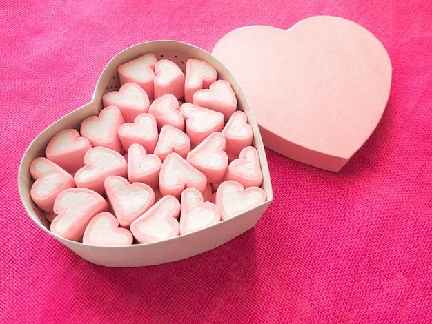 Marshmallow rosa in una confezione regalo a forma di cuore su tela rosa