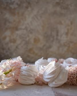 Marshmallow russo e fiori primaverili su sfondo scuro