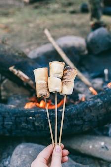 Marshmallow su un bastone sopra il fuoco cucinare marshmallow in fiamme
