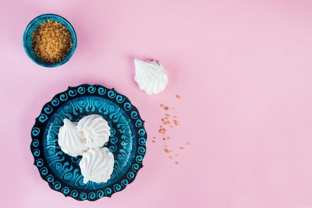 Marshmallow zephyr su piatto in ceramica blu con zucchero di canna o rosa