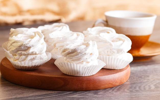 Marshmallows bianchi (zephyr) su una tavola di legno rotonda con una tazza di caffè