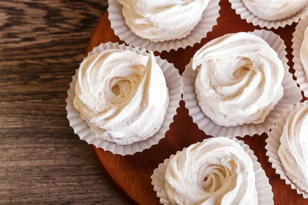 Marshmallows bianco (zephyr) su una tavola di legno rotonda