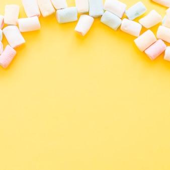 Marshmallows morbidi oltre il bordo di sfondo giallo