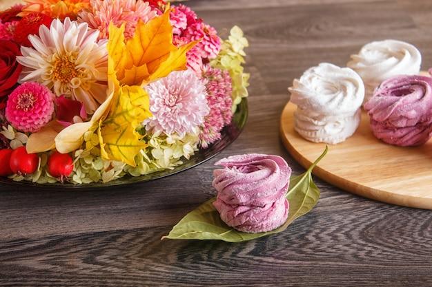 Marshmallows rosa e bianco (zephyr) su una tavola di legno rotonda con composizione floreale