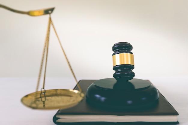 Martelletto con scala di equilibrio in ottone dorato su boook. diritto immobiliare e immobiliare.