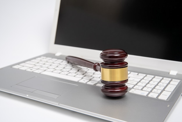 Martelletto del giudice in legno su un computer portatile d'argento