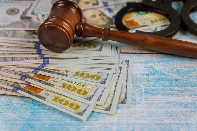 Martelletto del martello del giudice con le manette nelle banconote in dollari.
