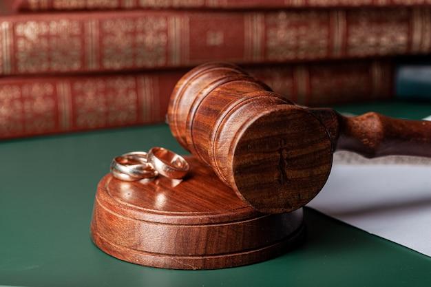Martelletto di legge e fedi nuziali sul tavolo