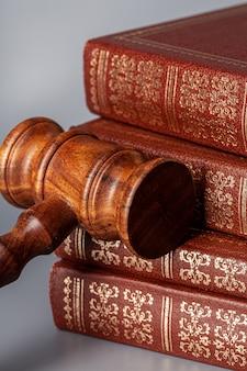 Martelletto di legno marrone con pila di libri sul tavolo grigio