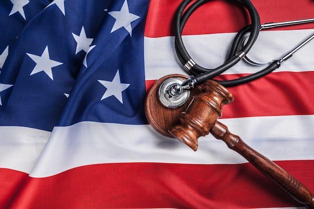 Martelletto e stetoscopio sulla bandiera nazionale degli stati uniti. concetto di medicina legale. pratica medica giudiziaria