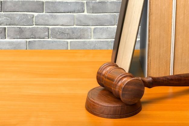 Martelletto in legno e libri sul tavolo di legno